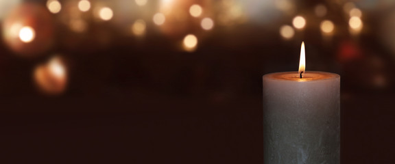 Burning candle with golden bokeh