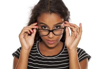 beautiful young dark skinned woman posing with eyeglasses