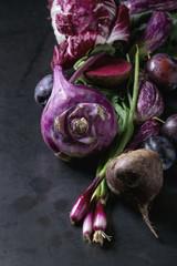 Assortment raw organic of purple vegetables mini eggplants, spring onion, beetroot, radicchio salad, plums, kohlrabi, flower salt over dark metal background. Close up with space