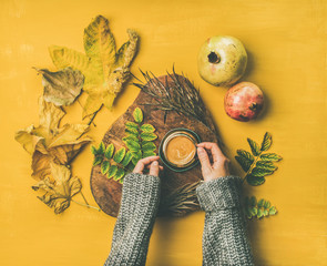 Autumn morning coffee concept. Flat-lay of woman' s hands in grey woolen sweater holding cup of espresso over mustard yellow background with dried fallen leaves and pomegranates around, top view