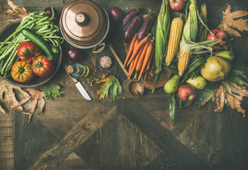 Fall cooking background. Ingredients for Thanksgiving day dinner. Flat-lay of green beans, corn cobs, carrot, tomatoes, eggplants, fruits and fallen leaves over wooden table, top view, copy space