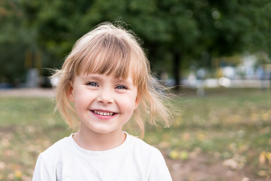 Portrait of a small laughing blond girl in nature with blurred background
