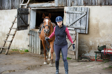 Horserider is walking with horse outdoors in autumn