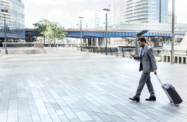 Businessman walking through the city with rolling suitcase and cell phone