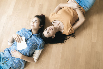 Two women lying on the floor holding photos