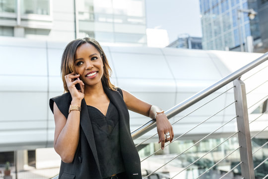 Smiling woman talking on the phone in the city