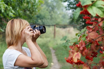 Young woman holding digital camera and taking pictures of viburnum branches