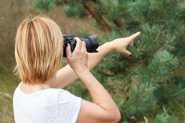 Young woman holding digital camera and taking pictures