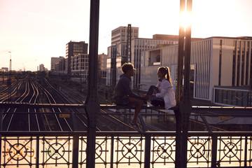 Germany, Munich, Young couple sitting on bridge, enjoying sunset
