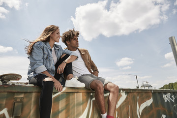 Young couple sitting on a wall