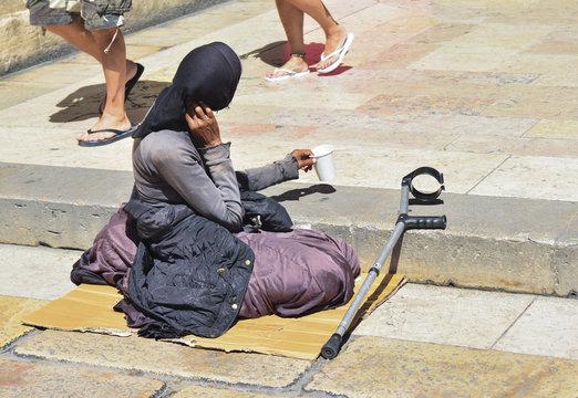 Poor woman begging in the street
