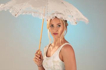 Frau mit ernstem Blick unter Sonnenschirm in weiß
