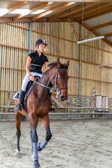 belle jeune fille travaillant son cheval en manège