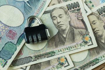 selective focus on combination lockpad on pile of japanese yen banknotes as financial safe haven or security concept