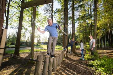 Confident Mature Man Crossing Log Bridge In Forest