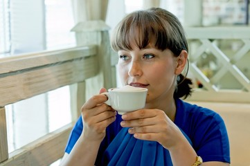 Young woman drinks coffee at a cafe, coffee break, leisure concept