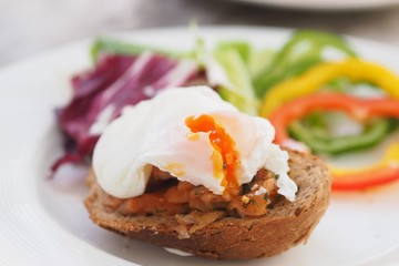 Healthy Breakfast with Wholemeal Bread Toast and Poached Egg with fresh Vegetables on dish.