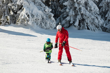 Little boy and ski trainer