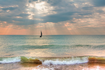 Lone yacht sailing in the Aegean sea at sunset