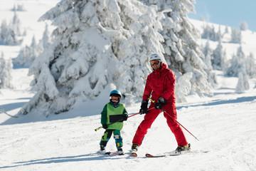 Ski instructor teaching little boy skiing