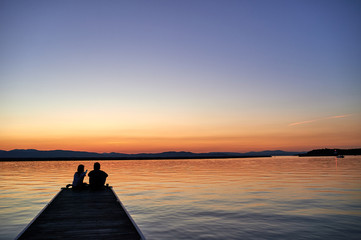 Couple on a pier at sunset silhouette