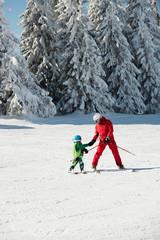 Ski trainer helping little boy