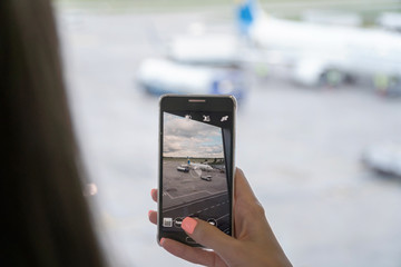 Close up of woman hands taking photo of plane. Travel Concept