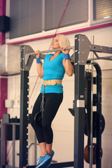 Bodybuilding. Strong fit woman exercising in a gym - doing pull-ups with weight
