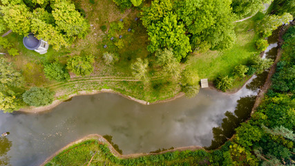 Top view of a small lake in a green forest. Aerial view.