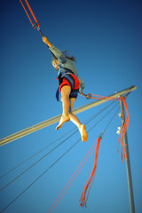Little girl on bungee trampoline with cords