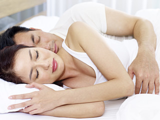 asian couple sleeping in bed at home or in a hotel room.