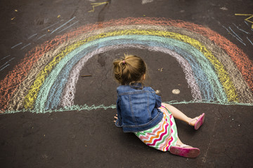 Girl drawing rainbow on asphalt