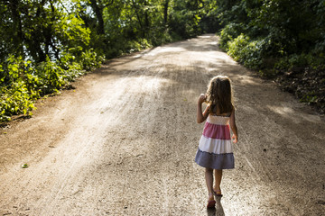 Rear view of girl walking on dirt road amidst trees in forest