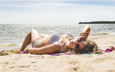Woman in bikini lying on sand at beach against sky during summer