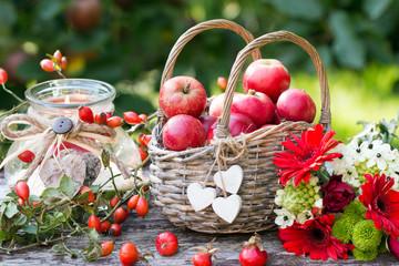 Herbstdekoration mit Äpfel im Weidenkorb,Herbstblumen und Hagebutten als Kartenmotiv