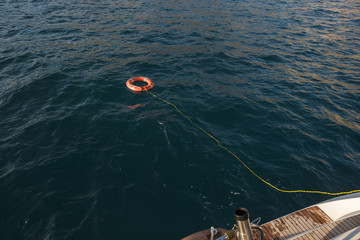 High angle view of inflatable ring attached with rope on boat in sea