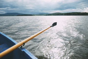 Oar in canoe on sea against cloudy sky
