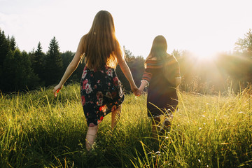 Rear view of lesbian couple holding hands while walking on grassy field during sunset
