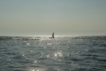 Silhouette of man and dog in sea