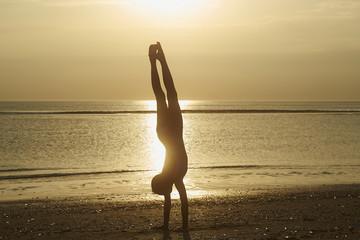 Full length of silhouette girl doing handstand at beach against sky during sunset