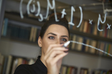 Businesswoman writing formula on glass wall at office