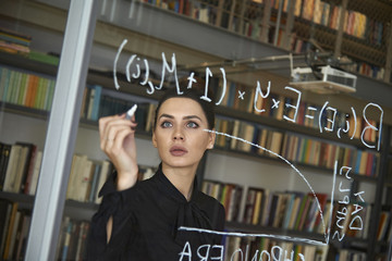 Serious businesswoman writing formula on glass wall at office