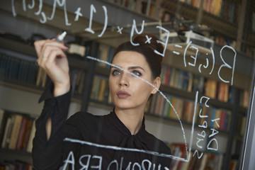 Businesswoman writing formula on glass wall