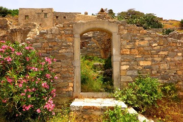 doorway to ruins with wildflowers on Spinalonga Island, Crete, Greece. Decay and rebirth concept