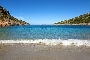 Blue sea cove with gentle surf breaking on beach. Solitude, escape, relaxation concept with copy space