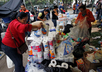 Residents remove donations of bottled water and items on the street next to at a collapsed building after earthquake in Mexico City