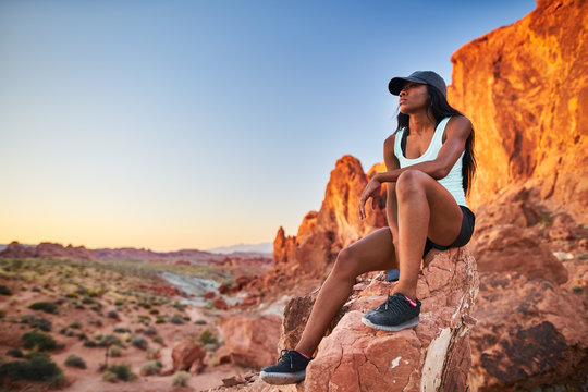 african american woman resting on rock at valley of fire park during hike