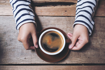Top view image of woman's hands holding and giving a cup of hot coffee on wooden vintage table