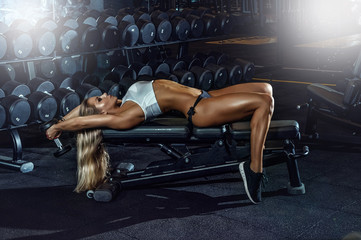 A beautiful girl is engaged in fitness in the gym. She lies on a bench and lifts a dumbbell.