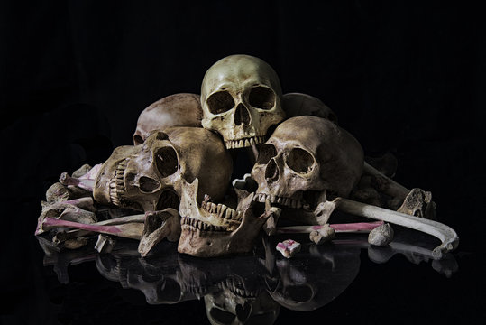 The human skull and pile of bones on black background, Halloween night, Still life style, art.